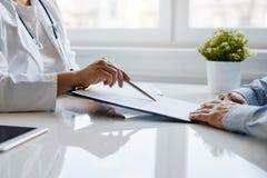 Den kvinnliga doktorn rekommenderar att fylla in ett medicinskt dokument royaltyfri bild
