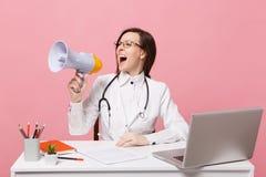 Den kvinnliga doktorn sitter på skrivbordarbete på datoren med den medicinska dokumenthållmegafonen i det isolerade sjukhuset på  royaltyfri fotografi