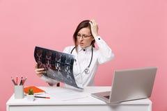 Den kvinnliga doktorn sitter på skrivbordarbete på datoren med den medicinska dokumenthållröntgenstrålen i det isolerade sjukhuse royaltyfria foton