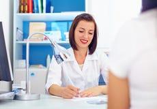 Den kvinnliga doktorn skriver recepten till patienten Fotografering för Bildbyråer