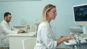 Den kvinnliga doktorn som dikterar ultraljudet, resulterar till hennes manliga kollega med bärbara datorn stock video