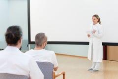 Den kvinnliga doktorn står framme av tomt ge sig för whiteboard arkivfoton
