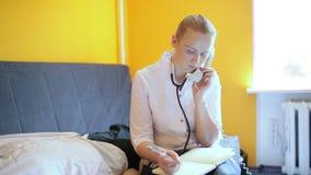 Den kvinnliga doktorn talar på telefonen och gör anmärkningar. arkivfilmer