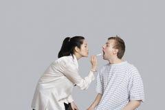 Den kvinnliga doktorn undersöker patientens hals arkivfoton