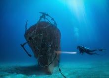 Den kvinnliga dykaren undersöker en sjunken skeppsbrott på de Maldiverna öarna royaltyfri bild