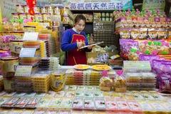 Den kvinnliga efterrättgodisen shoppar säljaren som räknar hennes gods arkivbild