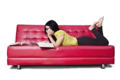 Den kvinnliga eleven som studerar och, läser böcker på soffan Royaltyfria Bilder