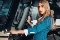 Den kvinnliga flygvärdinnan poserar mot helikoptern royaltyfri bild
