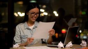 Den kvinnliga formgivaren som tillfredsst?lls med, skissar att rymma papper och att le, kreativitet arkivbilder