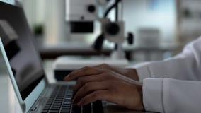 Den kvinnliga forskaren räcker maskinskrivning på bärbara datorn som arbetar på experimentell forskning i labb fotografering för bildbyråer