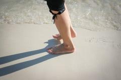 Den kvinnliga foten går på stranden royaltyfri bild