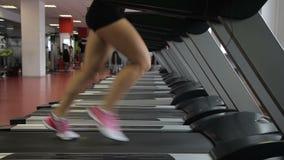 Den kvinnliga foten i rinnande skor kör längs trampkvarnen idrottshallen stock video