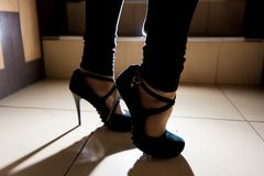 den kvinnliga foten i svart hög-heeled skor royaltyfria bilder