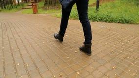 Den kvinnliga foten i svarta skor och jeans är på vägen stock video