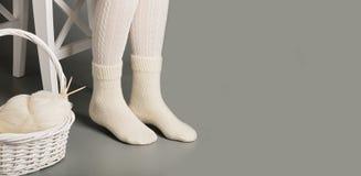 Den kvinnliga foten i vit stack strumpor och sockor nära korgen med garn och handarbete royaltyfria bilder