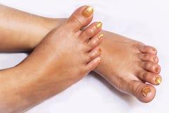 Den kvinnliga foten med f?rsiktigt pedicured trendigt guld- spikar visat i den korsade positionen royaltyfri bild