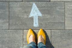 Den kvinnliga foten med pilen målade på asfalten Arkivfoto