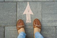 Den kvinnliga foten med pilen målade på asfalten Royaltyfri Fotografi