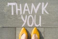 Den kvinnliga foten med text tackar dig som är skriftlig på den gråa trottoaren fotografering för bildbyråer