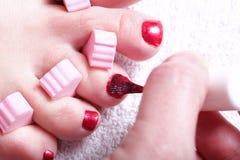 Den kvinnliga foten rött polerat spikar fotografering för bildbyråer