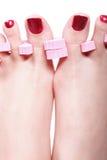 Den kvinnliga foten rött polerat spikar arkivfoto