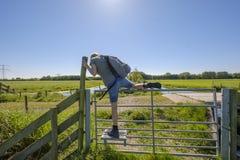 Den kvinnliga fotvandraren klättrar över ett staket med ett specialt moment för fotgängare Arkivbilder