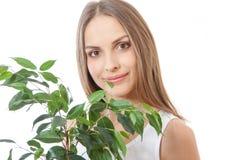 Den kvinnliga framsidan bakom grinar lövverkväxten arkivfoton