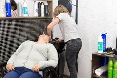 Den kvinnliga frisören tvättar klientkvinnans huvud, innan han klipper i en special vask i frisörens salong i den verkliga workin arkivbilder