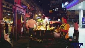 Den kvinnliga gatamatförsäljaren förbereder mat på den upptagna sukhumvitvägen i Bangkok, Thailand arkivfilmer