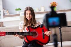 Den kvinnliga härliga bloggeren som spelar gitarren royaltyfria bilder
