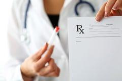 Den kvinnliga hållen för medicindoktorshanden och ger receptet Royaltyfri Fotografi
