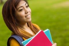 Den kvinnliga högskolestudenten med böcker parkerar in Fotografering för Bildbyråer