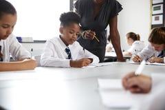 Den kvinnliga högstadiet handleder den Helping Students Wearing likformign som placeras runt om tabeller i kurs royaltyfri fotografi