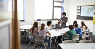 Den kvinnliga högstadiet handleder Standing By Table med studenter som undervisar kurs royaltyfri fotografi