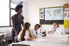 Den kvinnliga högstadiet handleder Standing By Table med studenter som undervisar kurs arkivfoton