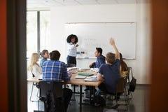 Den kvinnliga högstadiet handleder At Whiteboard Teaching matematikgrupp med eleven som frågar fråga royaltyfri foto