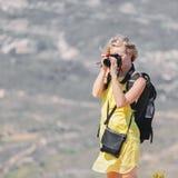 Den kvinnliga handelsresanden med en ryggsäck på henne som tycker om tillbaka sikterna från bergen av Montserrat i Spanien och, g Royaltyfri Bild