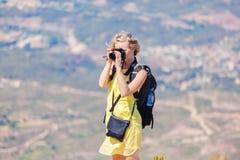 Den kvinnliga handelsresanden med en ryggsäck på henne som tycker om tillbaka sikterna från bergen av Montserrat i Spanien och, g Arkivbilder