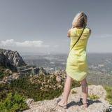 Den kvinnliga handelsresanden som tycker om sikterna från bergen av Montserrat i Spanien och, gör ett foto Arkivbilder