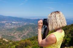 Den kvinnliga handelsresanden som tycker om sikterna från bergen av Montserrat i Spanien och, gör ett foto Arkivfoton