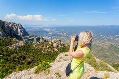 Den kvinnliga handelsresanden som tycker om sikterna från bergen av Montserrat i Spanien och, gör ett foto Royaltyfria Bilder