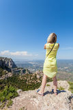 Den kvinnliga handelsresanden som tycker om sikterna från bergen av Montserrat i Spanien och, gör ett foto Fotografering för Bildbyråer