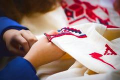Den kvinnliga handen broderar en modell på det vita materialet Fotografering för Bildbyråer