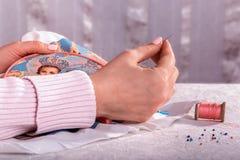 Den kvinnliga handen broderar med pärlor på beslag Arkivfoton