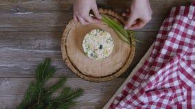 Den kvinnliga handen dekorerade sallad med en kvist av salladslöken stock video