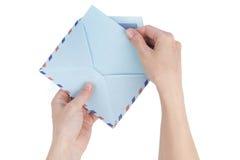 Den kvinnliga handen drar en bokstav ut ur kuvertet flygpost Arkivbilder