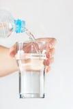 Den kvinnliga handen häller mineralvatten in i ett exponeringsglas från flaskan Royaltyfri Fotografi