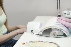 Den kvinnliga handen i en lampa för spikar uttorkning Salonginre royaltyfria foton