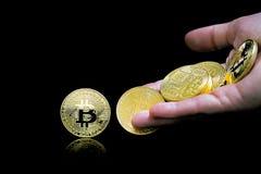 Den kvinnliga handen kastar guld- bitcoin Bitcoins på en svart bakgrund Bitcoins och nytt faktiskt pengarbegrepp Bitcoin är en ny royaltyfri fotografi