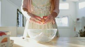 Den kvinnliga handen knäcker ett nytt ägg vid kniven arkivfilmer